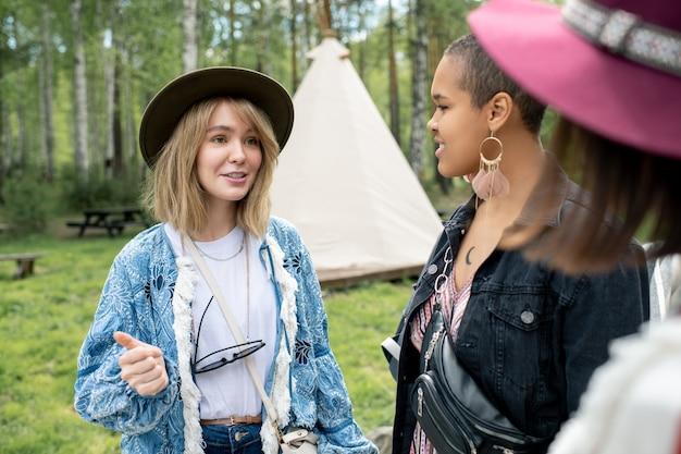 Hübsches blondes mädchen im hut, das mit freunden auf dem festivalcampingplatz plaudert, sie planen freizeit auf dem land