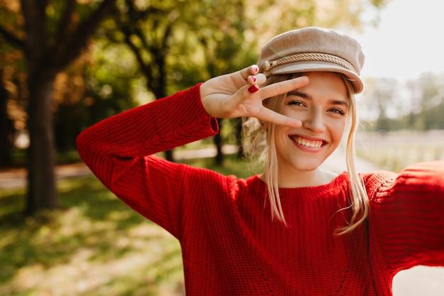 Hübsches blondes mädchen im stilvollen hut und im roten pullover, der mit lächeln aufwirft, um ein selfie im park zu machen.