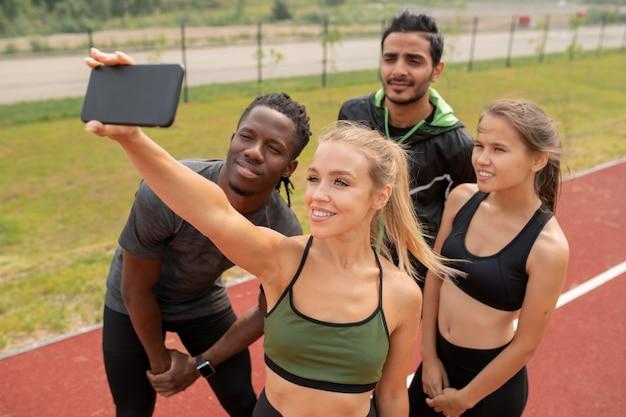 Hübsches blondes mädchen in der aktivkleidung, das selfie mit ihren freunden macht, die in der nähe auf freiluftstadion stehen