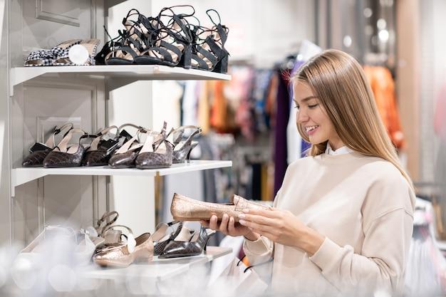Hübsches blondes mädchen in der freizeitkleidung, das paar der neuen schuhe im einkaufszentrum wählt, während es es auf verkaufszeit besucht