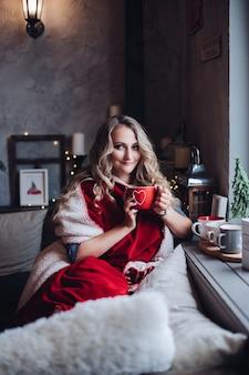 Hübsches blondes mädchen in rot eingewickelt in plaid, das weihnachtsmorgen mit tasse kaffee am fenster genießt.