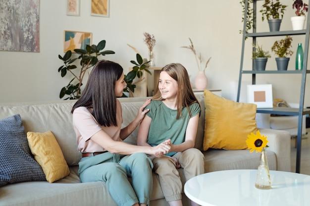 Hübsches blondes mädchen mit einem zahnigen lächeln, das ihre mutterhand hält, während beide frauen auf einer weichen, bequemen couch im wohnzimmer sitzen?