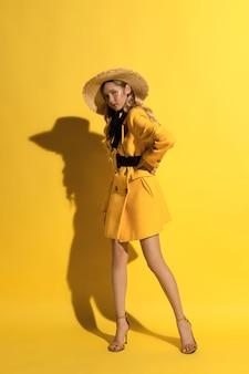 Hübsches blondes mädchen mit sommersprossen im gelben outfit und strohhut auf gelbem hintergrund