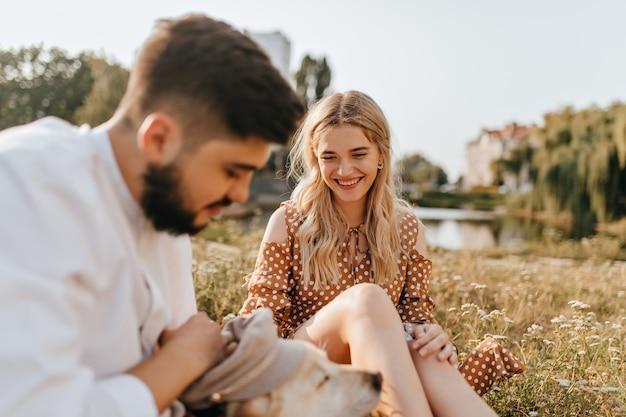 Hübsches blondes mädchen und ihr freundlicher ehemann ruhen sich auf gras aus und spielen mit ihrem haustier. paar posiert vor dem hintergrund des sees.