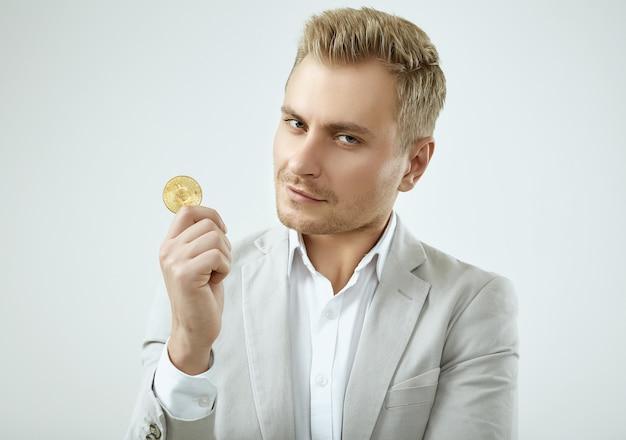 Hübsches blondes mannmodell in einer grauen klage der mode hält ein bitcoin