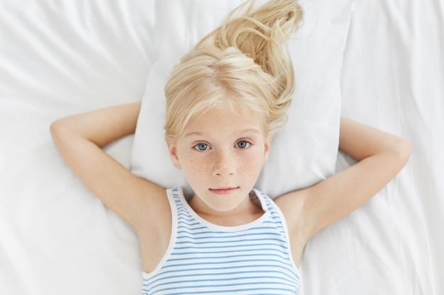 Hübsches blondes sommersprossiges blauäugiges mädchen, das im bett auf weißer bettwäsche liegt und direkt mit ihren sanft leuchtenden augen schaut