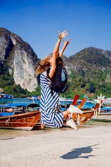 Hübsches braunes rucksacktouristenmädchen, das an der heißen tropischen phi phi-insel aufwirft, erstaunliche ansicht auf lokalen booten und bergen.