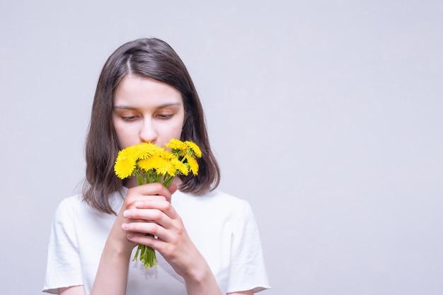 Hübsches brünettes mädchen, das gelbe wildblumen von löwenzahn hält und ihr aroma auf hellem hintergrund einatmet, kopienraum. helle frühlingsblumen. liebe, romantik, hochzeitskonzept