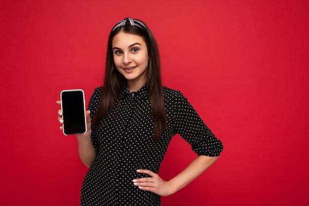 Hübsches brünettes mädchen, das isoliert über roter wand steht und lässige, stilvolle schwarze kleidung trägt, die ein mobiltelefon mit leerem bildschirm für den ausschnitt mit blick auf die kamera zeigt