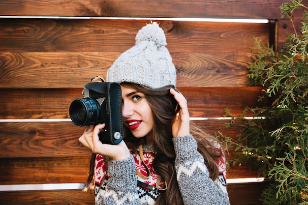 Hübsches brünettes mädchen des nahaufnahmeporträts in der strickmütze und im warmen pullover, die ein foto auf kamera auf holz machen. sie lächelt.