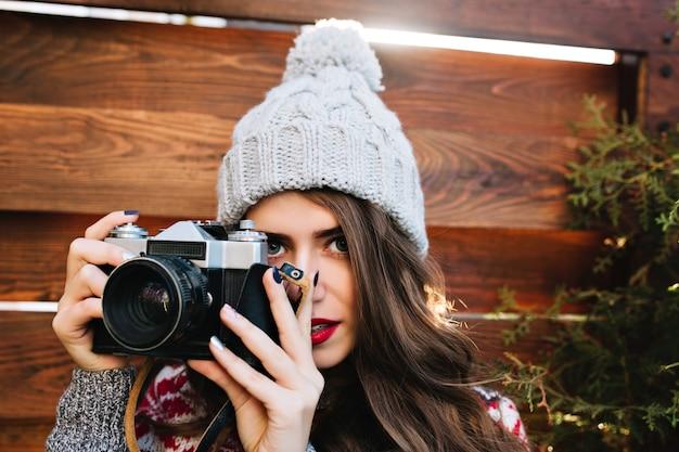 Hübsches brünettes mädchen des nahaufnahmeporträts mit langen haaren in der strickmütze, die ein foto auf kamera auf hölzernem außen macht.