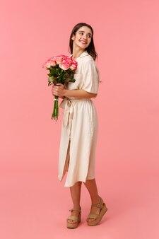Hübsches brünettes mädchen des vertikalen porträts in voller länge am romantischen datum, das schöne blumenstraußblumen empfängt, rosen hält und mit entzücktem weichem und zartem lächeln nach hinten schaut, stehende rosa wand