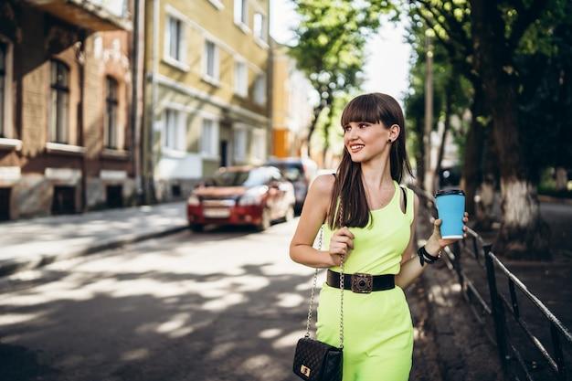 Hübsches brünettes mädchen im grünen kleid mit tasse kaffee, der draußen auf der straße geht