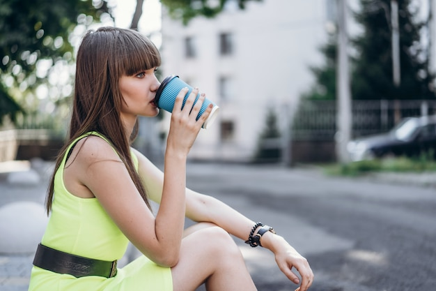 Hübsches brünettes mädchen im grünen kleid mit tasse kaffee, der draußen auf der straße sitzt