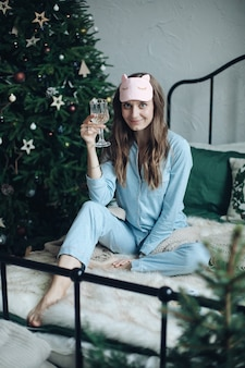 Hübsches brünettes mädchen im pyjama und in der schlafmaske, die glas champagner auf bett sitzend heben. weihnachten.