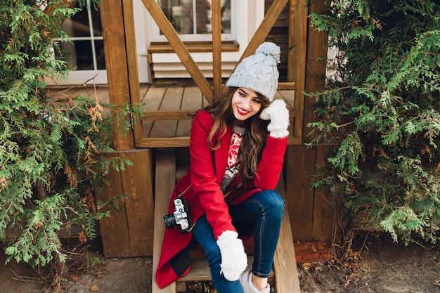 Hübsches brünettes mädchen im roten mantel, in der strickmütze und in den weißen handschuhen, die auf holztreppen im freien sitzen. sie hat lange haare und lächelt zur seite.