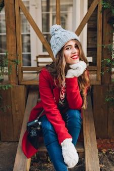 Hübsches brünettes mädchen im roten mantel, in der strickmütze und in den weißen handschuhen, die auf holztreppen im freien sitzen. sie hat lange haare und lächelt.