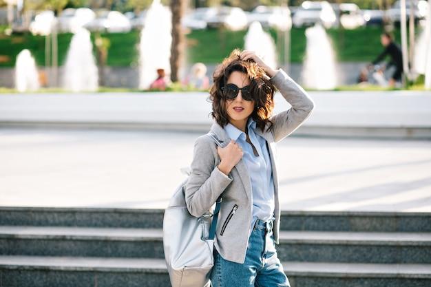 Hübsches brünettes mädchen in der sonnenbrille posiert vor der kamera in der stadt. sie trägt hemd, jeans, jacke und tasche. ihre kurzen haare fliegen im wind.