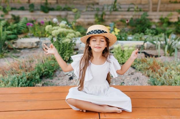 Hübsches brünettes weibliches kind im strohhut, das nahe blumenbeet in lotushaltung mit geschlossenen augen sitzt. kleines mädchen im weißen kleid, das yoga im garten tut