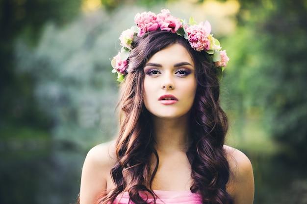 Hübsches brunette-mädchen mit lockiger frisur im freien. modefrau im park. make-up, dunkles gewelltes haar, blumen