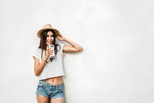 Hübsches brunettemädchen im hut mit kaffee und weißer wand hinten, kopienraum.