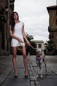Hübsches brunettemädchen im weißen kleid und in einem windhund mitten in einer straße