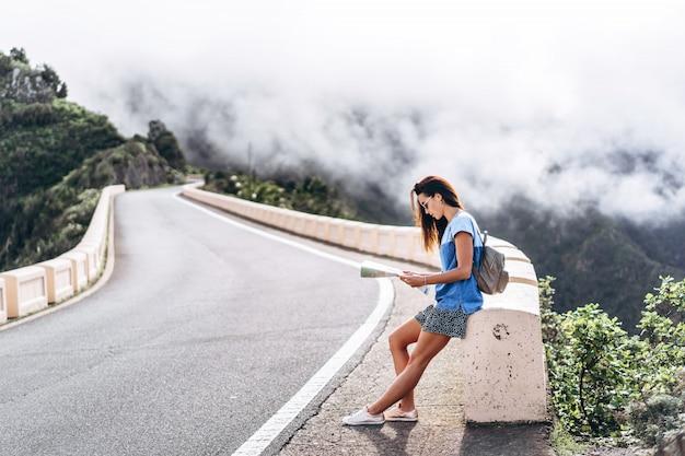 Hübsches brunettemädchen in der sonnenbrille im freien in den bergen mit karte.