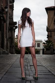 Hübsches brunettemädchen mit weißem kleid mitten in der straße