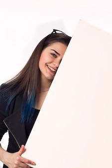 Hübsches brunettestudentenmädchen mit weißem brett