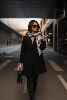 Hübsches business-modell der jungen frau mit elegantem schal auf dem kopf in modischer sonnenbrille in einem trendigen mantel mit schwarzer lederhandtasche steht auf der straße in der stadt. sexy mädchen, das draußen aufwirft. moderne dame.