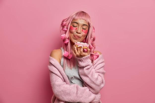Hübsches charmantes mädchen leckt lippen hält appetitlich köstlichen donut trägt kollagenpflaster unter den augen lockenwickler für lockige frisur warmen strickpullover