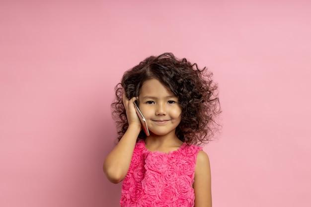 Hübsches dunkelhaariges kleines mädchen, das auf handy spricht. technologie, kommunikation, kinder, gadget-konzept