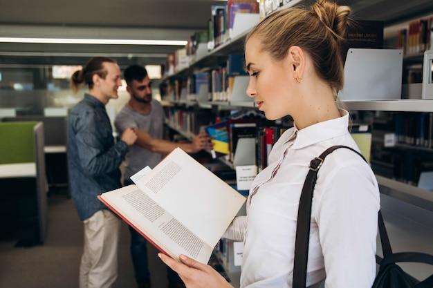 Hübsches durchdachtes mädchen sieht wie der student aus, der mit buch in der bibliothek einer universität steht