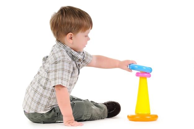 Hübsches einjähriges kleines baby, das mit bunter pyramide spielt