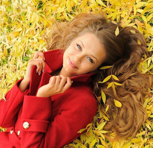 Hübsches frauenporträt, das auf gelben ahornblättern im park liegt, gekleidet in modischem rotem mantel