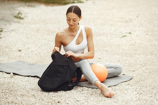 Hübsches frauentraining an einem sommerstrand. brünette macht yoga. mädchen in einem sportanzug.