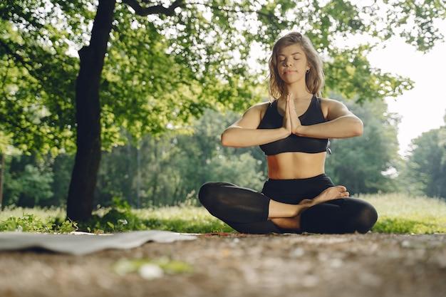 Hübsches frauentraining in einem sommerpark. brünette macht yoga. mädchen in einem sportanzug.