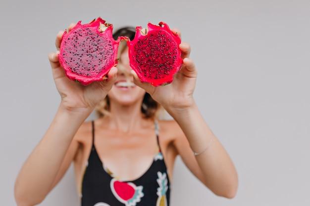 Hübsches gebräuntes mädchen, das rote pitaya hält. porträt des entspannten weiblichen modells, das mit drachenfrüchten aufwirft.