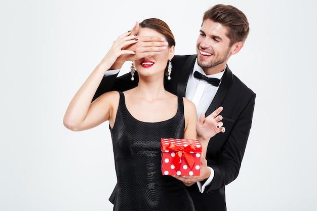 Hübsches geschäftspaar mit geschenk. mann macht überraschung