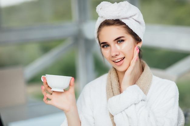 Hübsches gesicht. attraktives, lächelndes mädchen in der weißen robe, sitzend an der hotelterrasse und tasse kaffee oder tee halten. make-up-konzept.