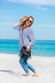 Hübsches glück junge frau, die lacht und spaß am sonnigen strand hat