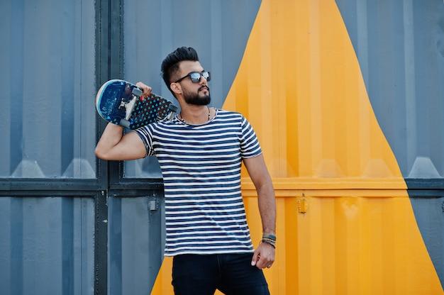 Hübsches großes arabisches bartmannmodell an abgestreiftem hemd warf im freien auf. moderner arabischer kerl an der sonnenbrille mit skateboard gegen gelb malte wand.