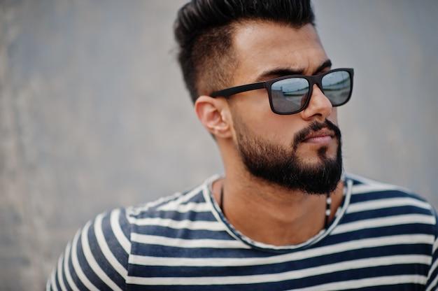 Hübsches großes arabisches bartmannmodell an abgestreiftem hemd warf im freien auf. moderner arabischer kerl an der sonnenbrille.