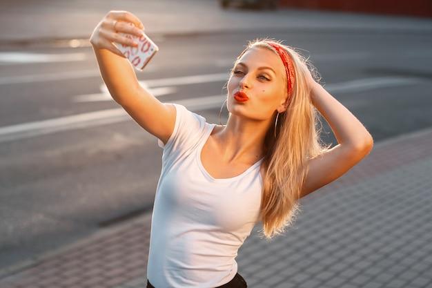 Hübsches hipster-mädchen, das selfie nimmt und entengesicht macht