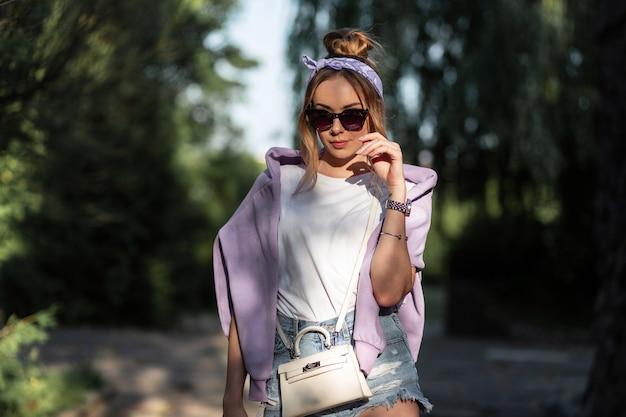 Hübsches hipster-mädchenporträt mit bandana und sonnenbrille in modischer sommerkleidung geht im freien spazieren