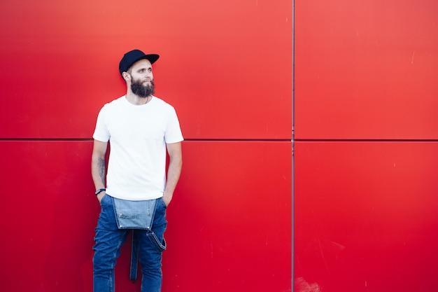 Hübsches hübsches männliches modell des hipsters mit bart, der weißes leeres t-shirt und eine baseballkappe mit platz für ihr logo trägt