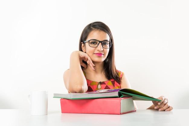 Hübsches indisches asiatisches collagenmädchen, das auf tablet mit stapel büchern studiert studying