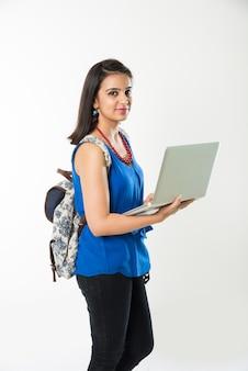 Hübsches indisches asiatisches college-mädchen, das laptop-computer mit tasche verwendet oder hält, stehend isoliert auf weißem hintergrund