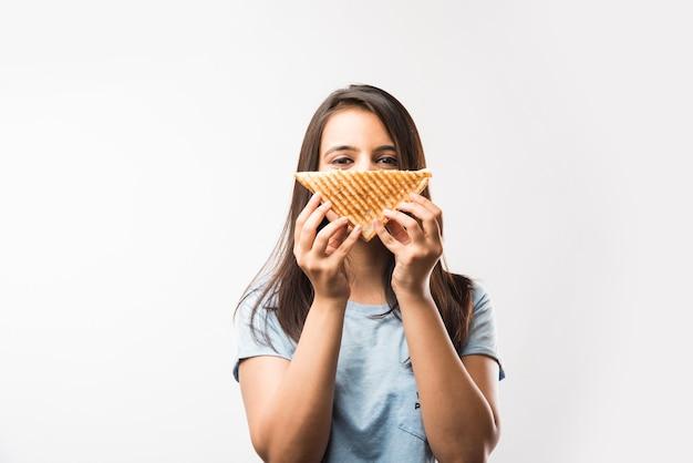 Hübsches indisches asiatisches junges mädchen, das gegrilltes sandwich isst und isoliert auf gelbem oder weißem hintergrund steht