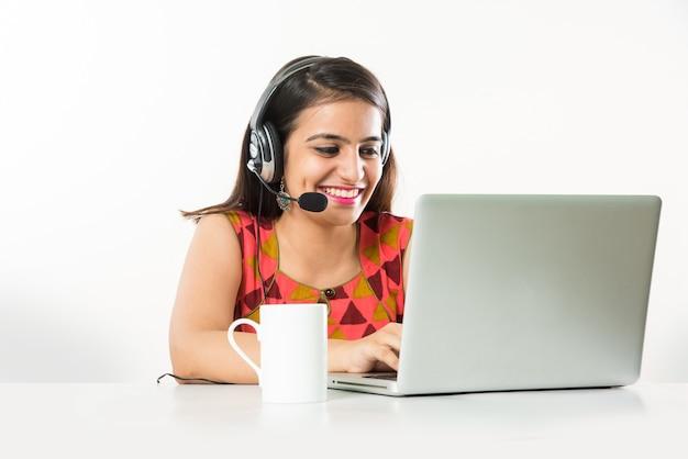 Hübsches indisches asiatisches mädchen oder bpo- oder call-center-mitarbeiter, der über kopfhörer mit laptop auf dem tisch spricht speaking